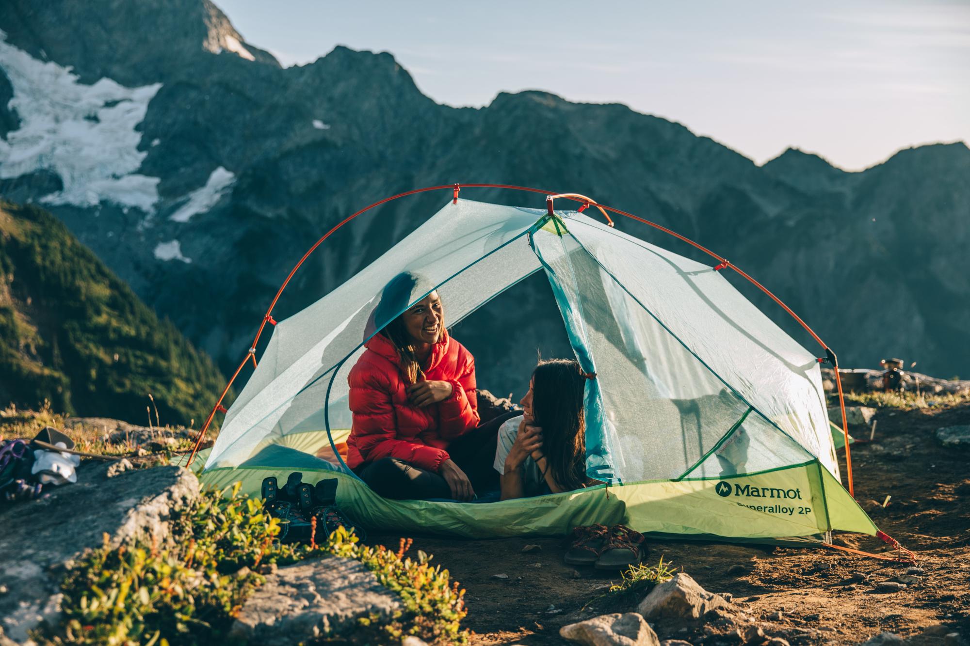 Eine junge Frau sitzt in einem Marmot Zelt und schaut lachend in die Kamera. Daneben liegt eine weitere junge Frau, ebenfalls lachend. Ihr Gesciht ist von der Kamera abgewandt. Im Hintergrund ist eine Bergkette.