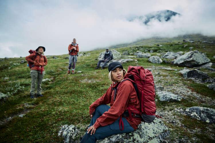 Im Vordergrund sitzt eine blonde Frau auf einem Felsen. Sie trägt eine rote Jacke und einen roten Rucksack. Im Hintergrund stehen versetzt zwei weitere Menschen in Outdoorkleidung. Alle schauen aus dem rechten Bildrand.