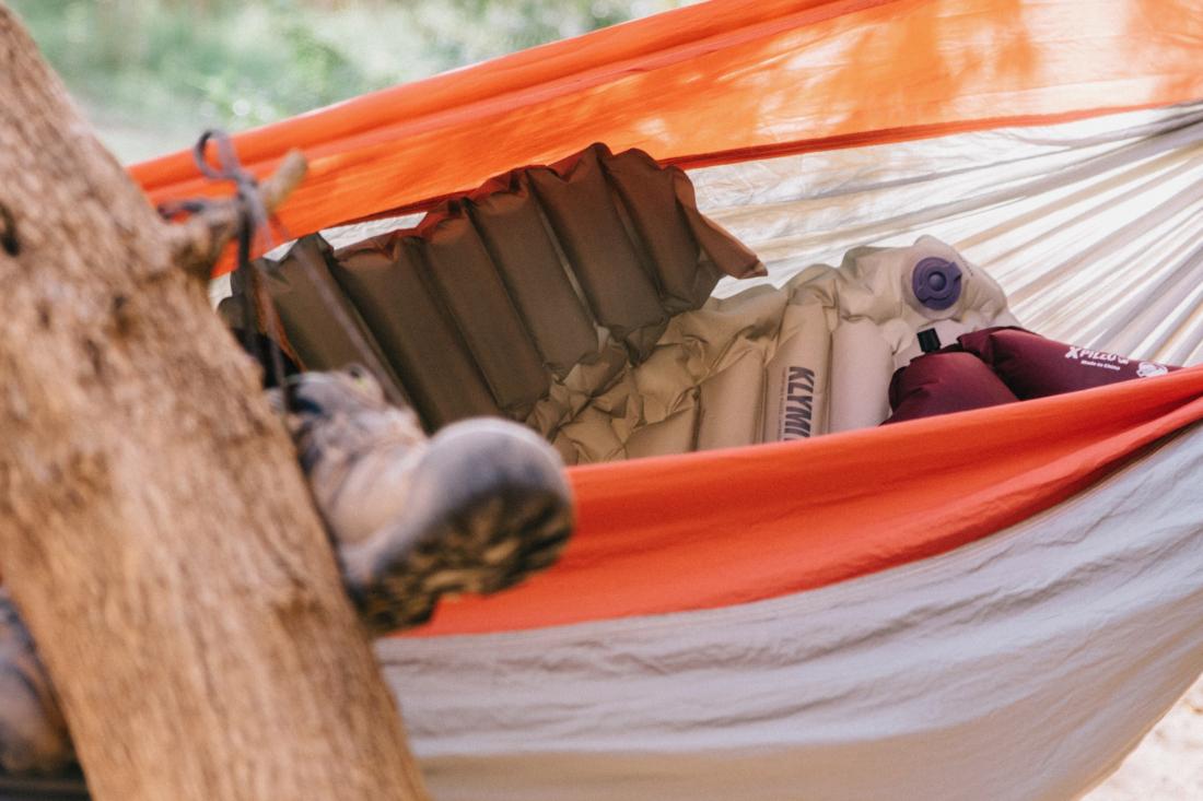 Eine Isomatte liegt in einer orangenen Hängematte. Unscharf im Vordergrund hängen Wanderschuhe an einem Baum.