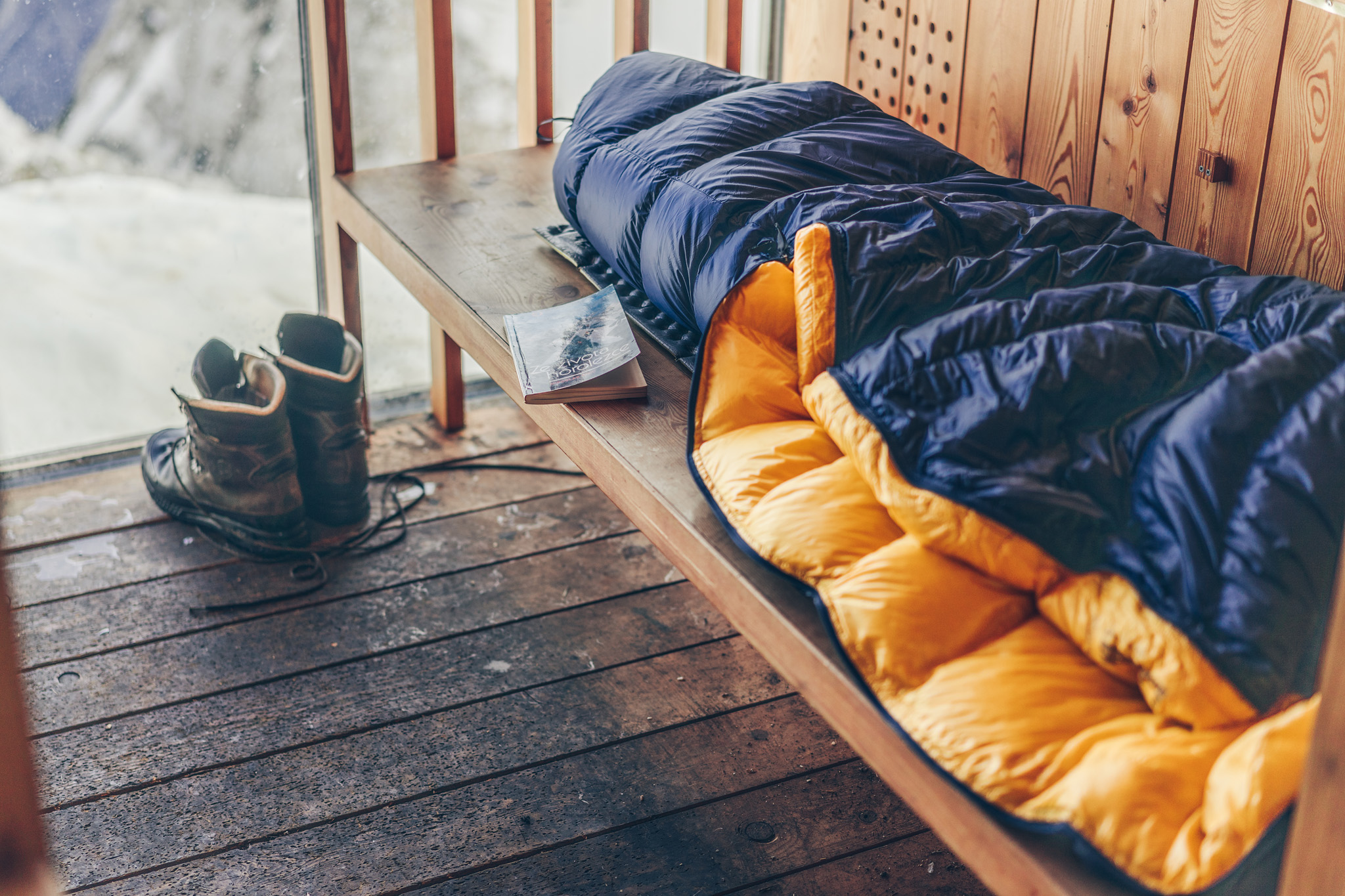 Ein blau-gelber Patizon-Daunenschlafsack liegt auf einer Holzbank in einer Berghütte. Wanderschuhe stehen im Hintergrund, daneben liegt ein Buch auf tschechisch