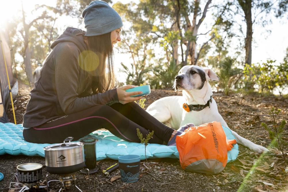 Eine Frau sitzt auf einer hellblauen Isomatte. Neben ihr liegt ein weiß-brauner Hund. Im Vordergund findet sich ein Packsack von Sea to Summit sowie ein Gaskocher mit Topf. Das Bild ist gegen das Licht aufgenommen.