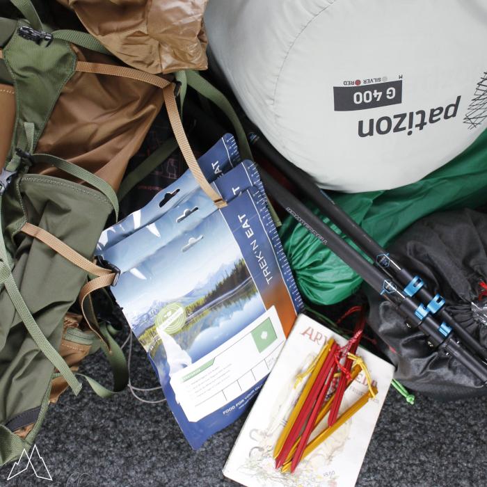 Ausrüstung auf dem Boden vor dem Rucksack