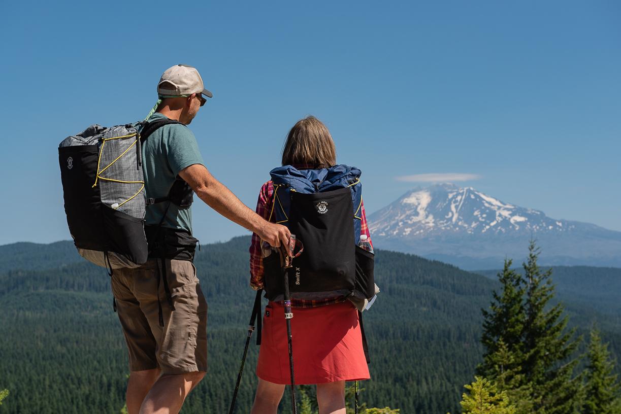 Zwei Menschen blicken zu einem schneebedeckten Berggipfel hinüber