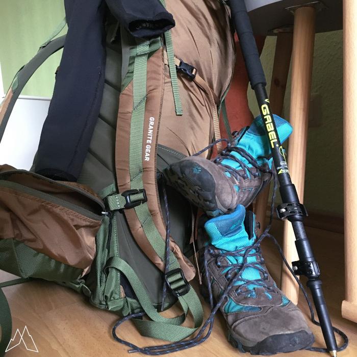 Rucksack, Wanderschuhe und Trekkingstock stehen in einem Raum