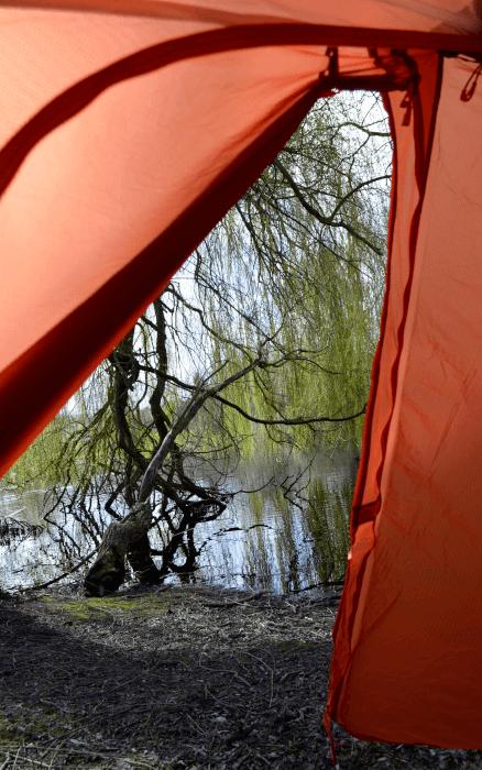 Blick aus dem orangenen Zelt aufgestellt am See