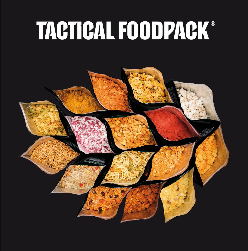 Geöffnete Tactical Foodpacks stehen in einer Gruppe zusammen. Sie sind in der Draufsicht fotografiert. Der Untergrund ist schwarz, nur der Beutelinhalt ist farbig.