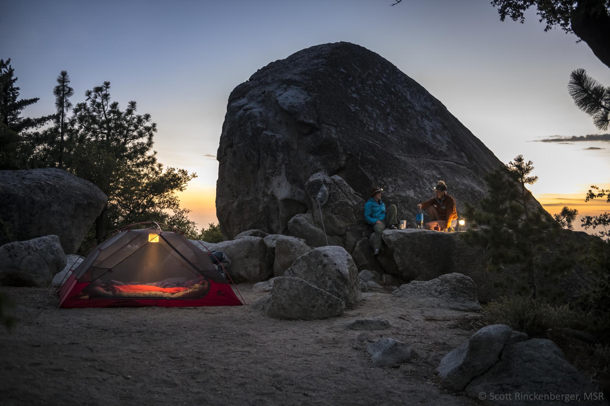 Ein MSR-Zelt steht in rauer, felsiger Landschaft. Die Dunkelheit bricht herein, die Wanderer haben es sich mit Lampen gemütlich gemacht.