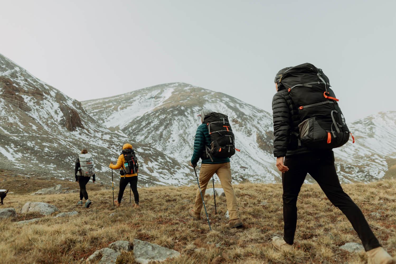 Eine Gruppe Wanderer laufen auf eine Bergkette zu. Sie tragen den Flex Capacitor von Sierra Designs