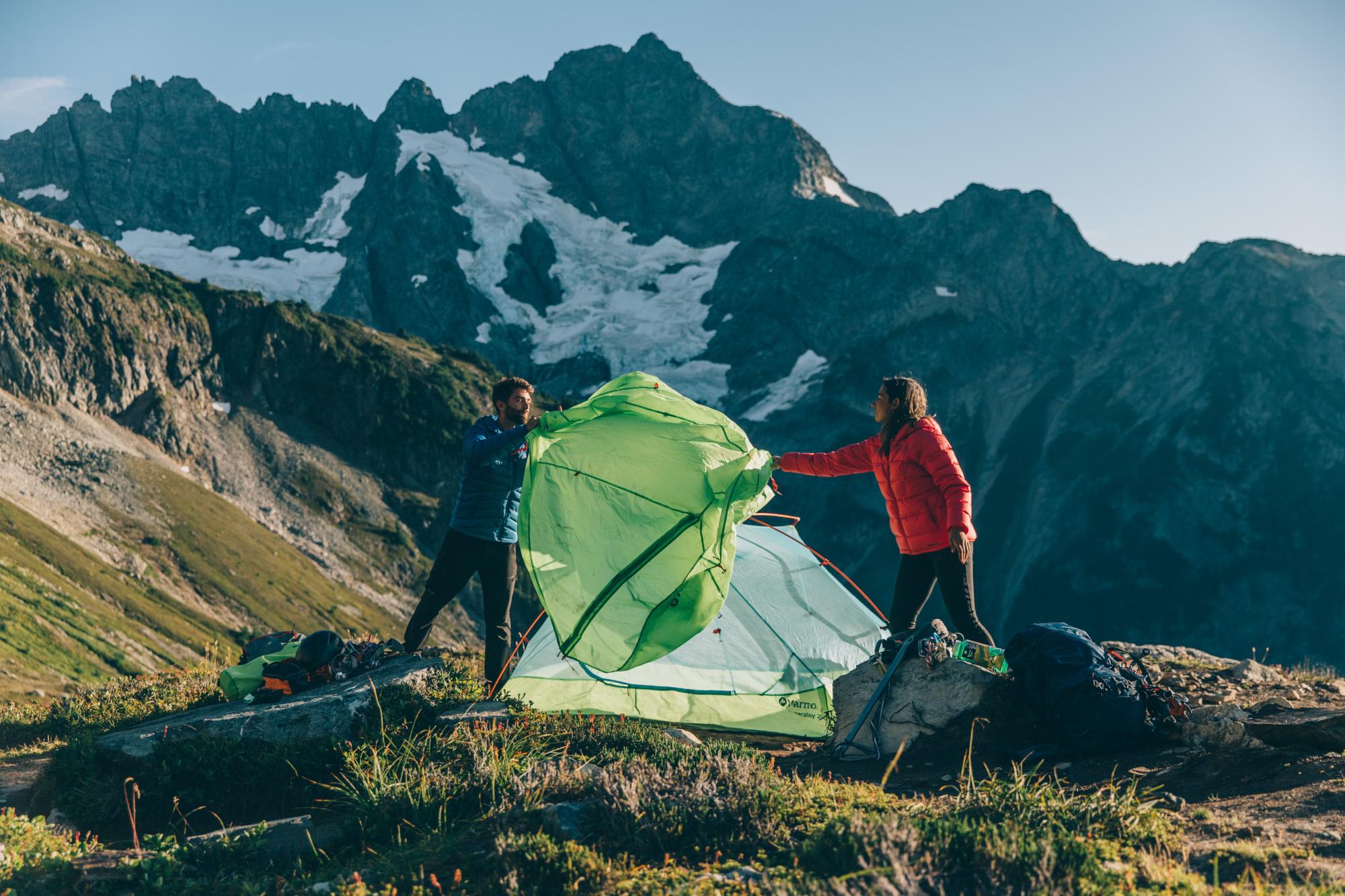 Eine Frau und ein Mann bauen gemeinsam ein Zelt von marmot auf. gerade werfen sie das Rainfly über das Gestänge. Im Hintergrund sind Berge.