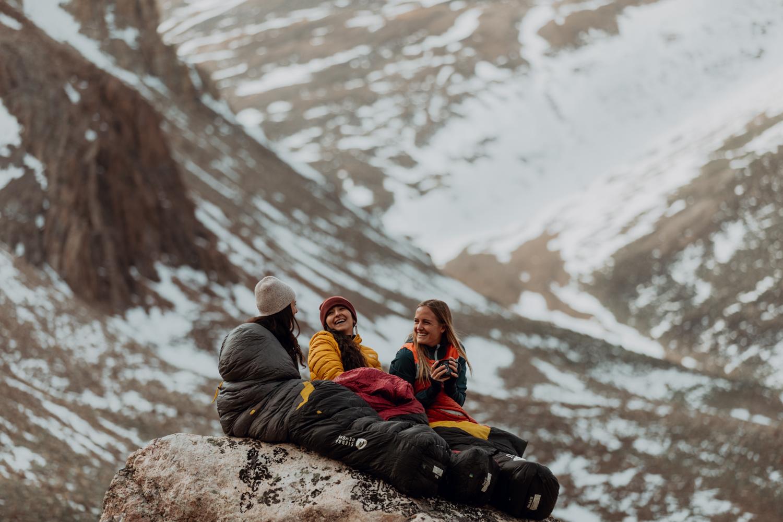 drei Frauen sitzen auf einem Felsen in den Bergen. Sie sind eingehüllt in Schlafsäcke von Sierra Designs