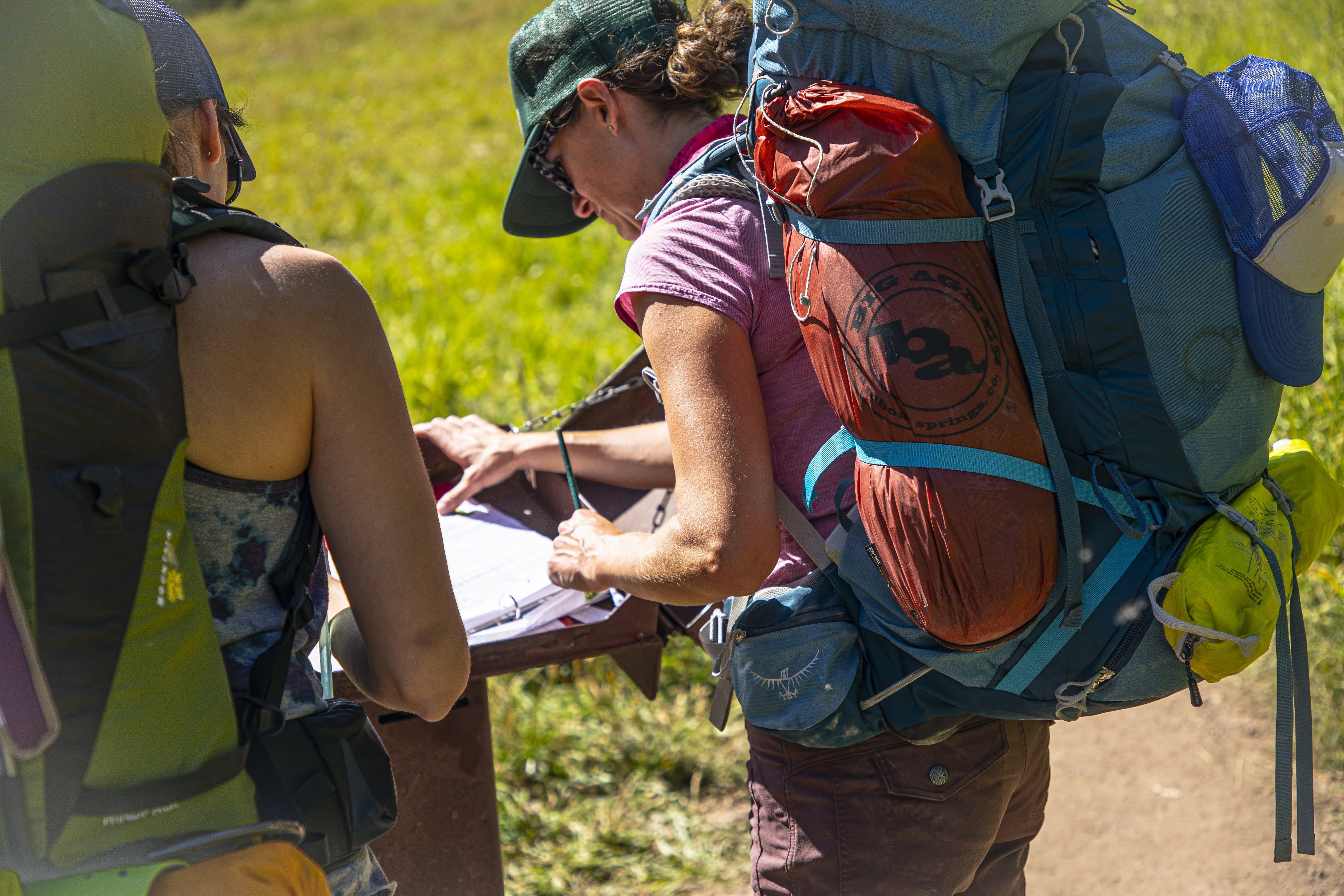 Eine Frau trägt einen Rucksack. Sie studiert eine Wanderkarte. In der Seitentasche des Rucksacks befindet sich ein verpacktes Big Agnes Zelt