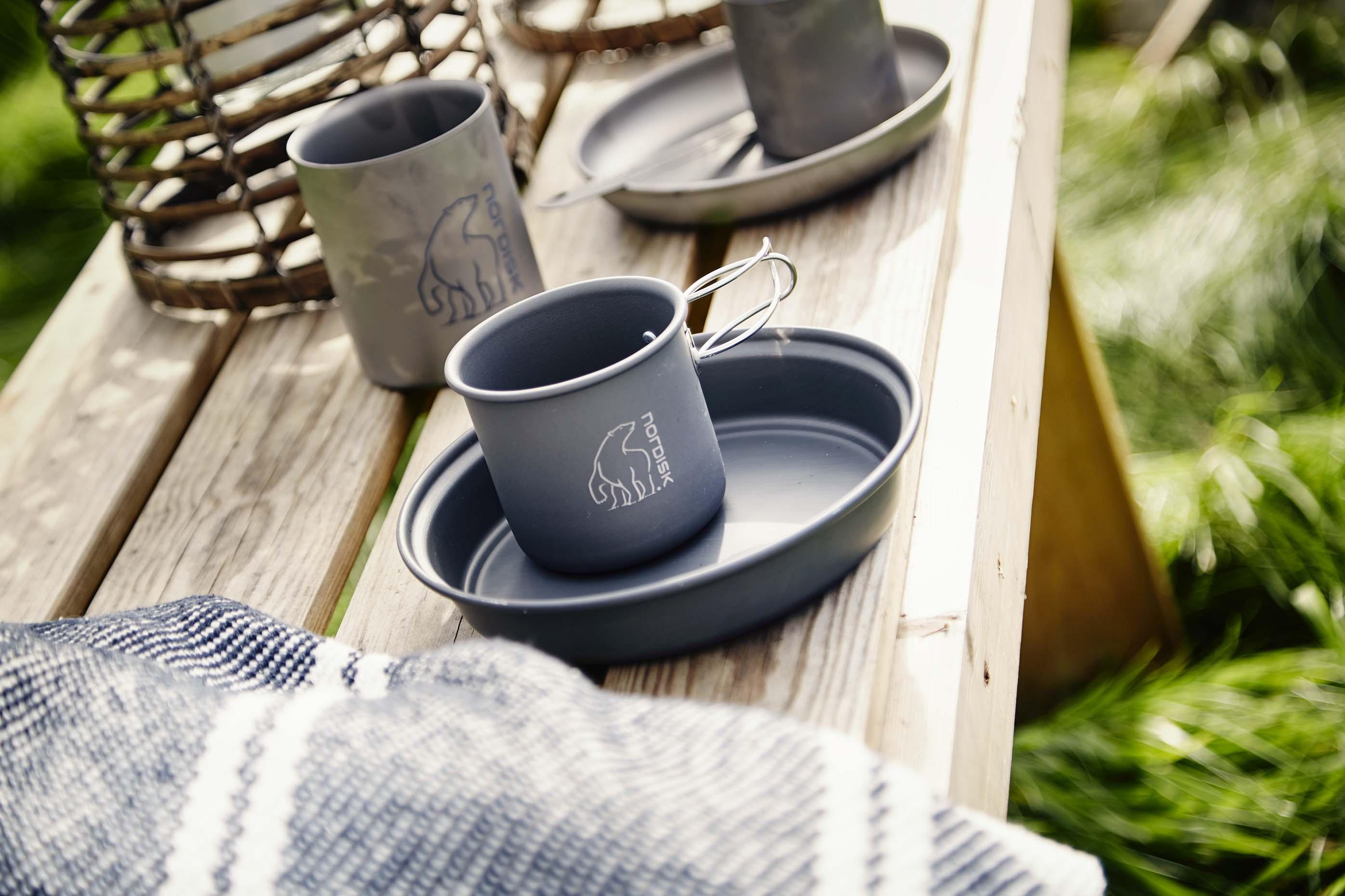Aluminium und Titangeschirr von Nordisk auf einer Holzbank