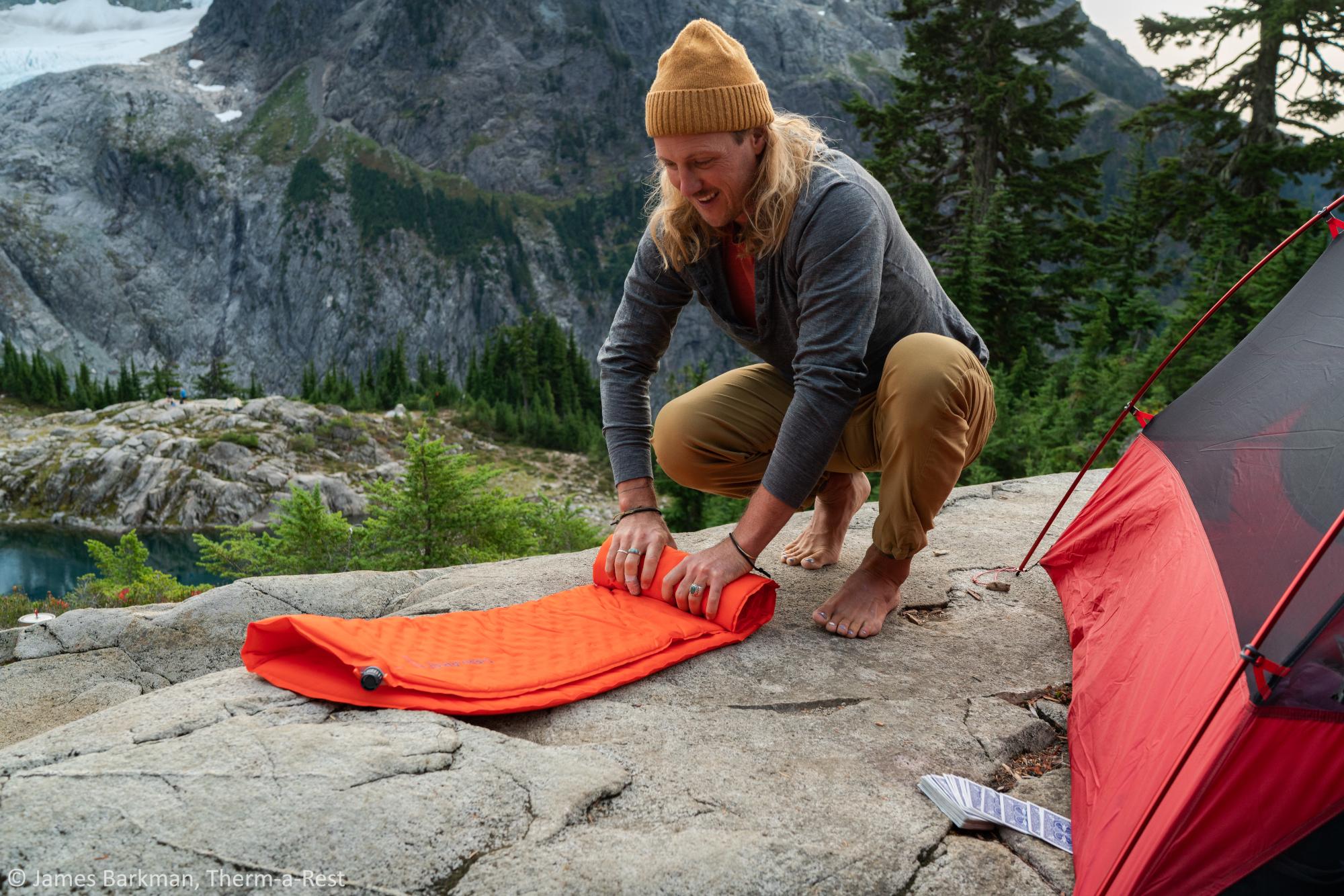 Ein junger Mann verpackt seine Isomatte von Therm-a-Rest auf ein super kleines Packmaß.