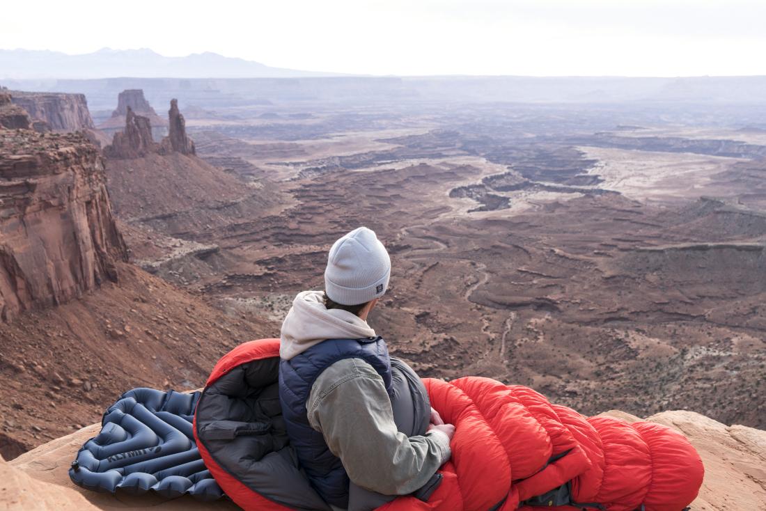 Ein Mann sitzt auf einer blauen Isomatte und ist in einen roten Schlafsack gehüllt. Er schaut von der Kamera weg. Er sitzt am Rand eines Plateaus und schaut über einen zerklüfteten Canyon aus rotem Gestein.