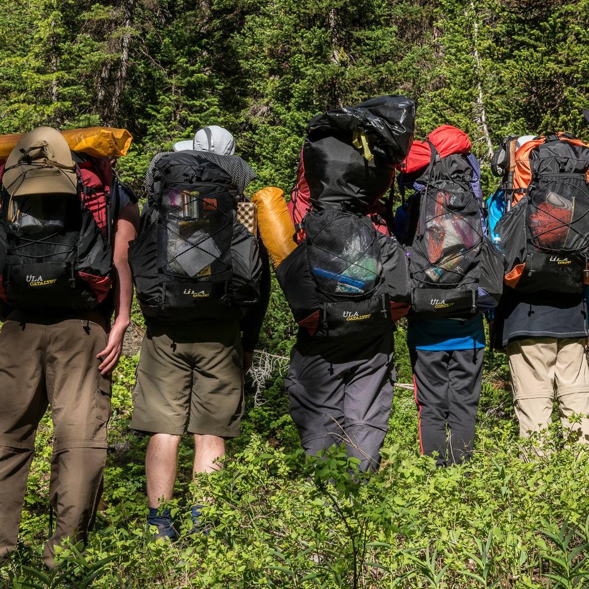 Eine Gruppe Menschen steht vor einem Wald. Alle tragen ULA Rucksäcke und sind von der Kamera abgewandt