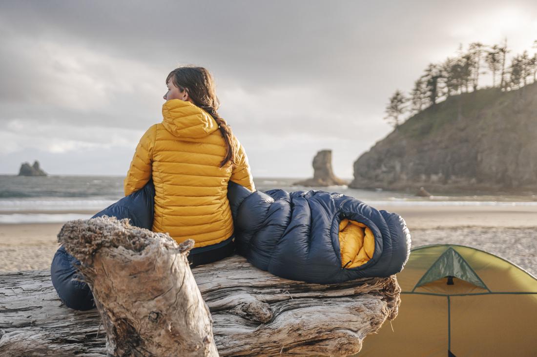 junge Frau in gelber Daunenjacke sitzt am Meer. Auf ihrem Schoß liegt ein blauer Daunenschlafsack von Patizon