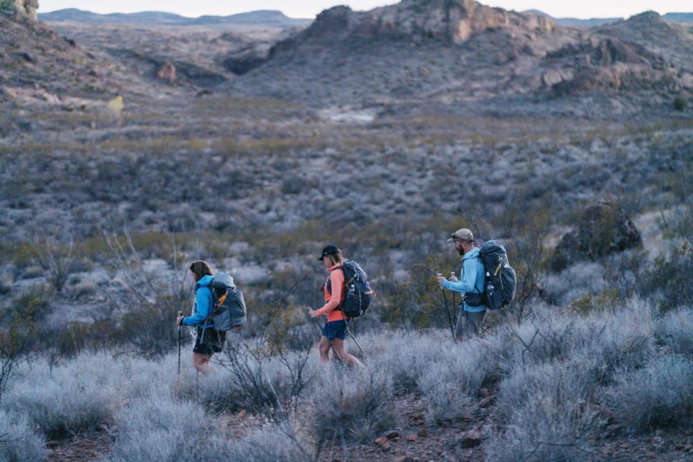 Drei Wandernde gehen durch eine halbwüstenartige Landschaft. Im Hintergrund sind Felsen zu sehen.