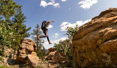 Ein Mann mit Rucksack springt von Felsen zu Felsen