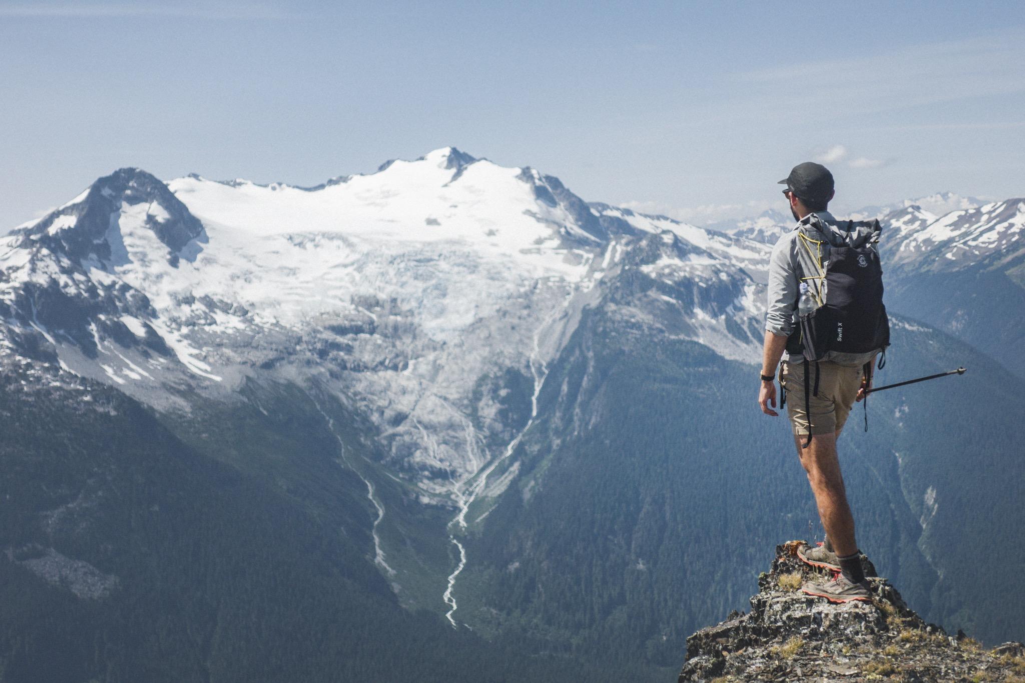Wanderer auf einem Felsvorsprung mit Blick über die Berge