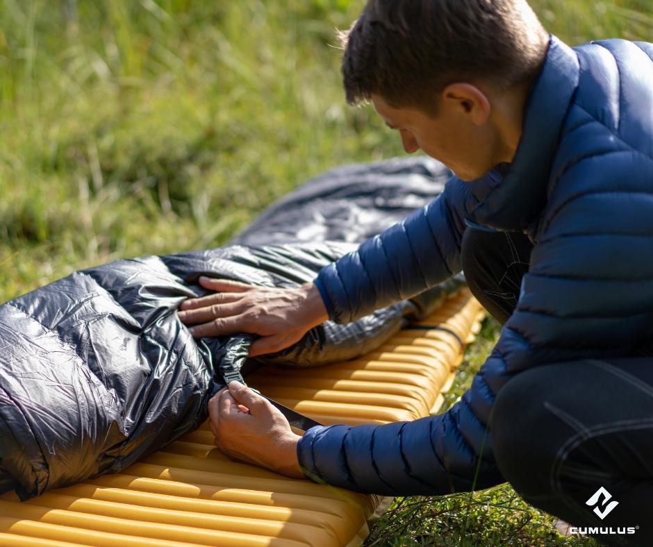 Ein Mann befestigt einen Cumulus-Schlafsack auf einer gelben Isomatte. Er befindet sich auf einer Wiese