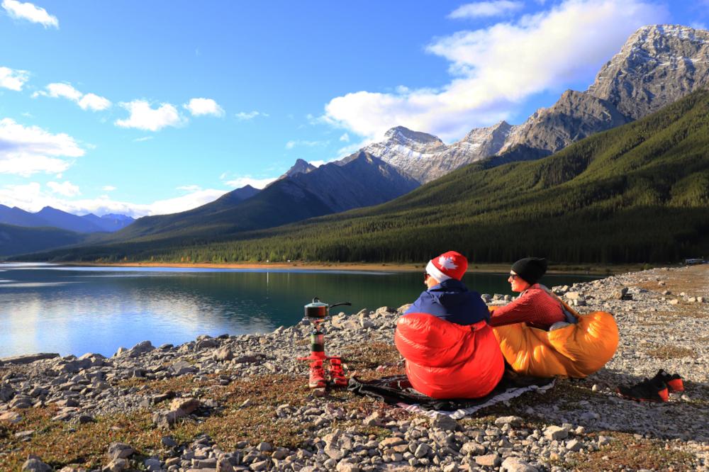 Zwei Menschen in roter und gelber Daunenjacke sitzen an einem Bergsee. Über ihren Knien liegen Schlafsäcke in blau von Patizon. Neben ihnen steht ein Kocher