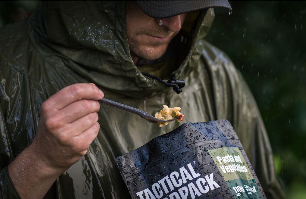 Ein Mann isst aus einem Tactical Foodpack. Es regnet.Das Gesicht ist nicht erkennbar