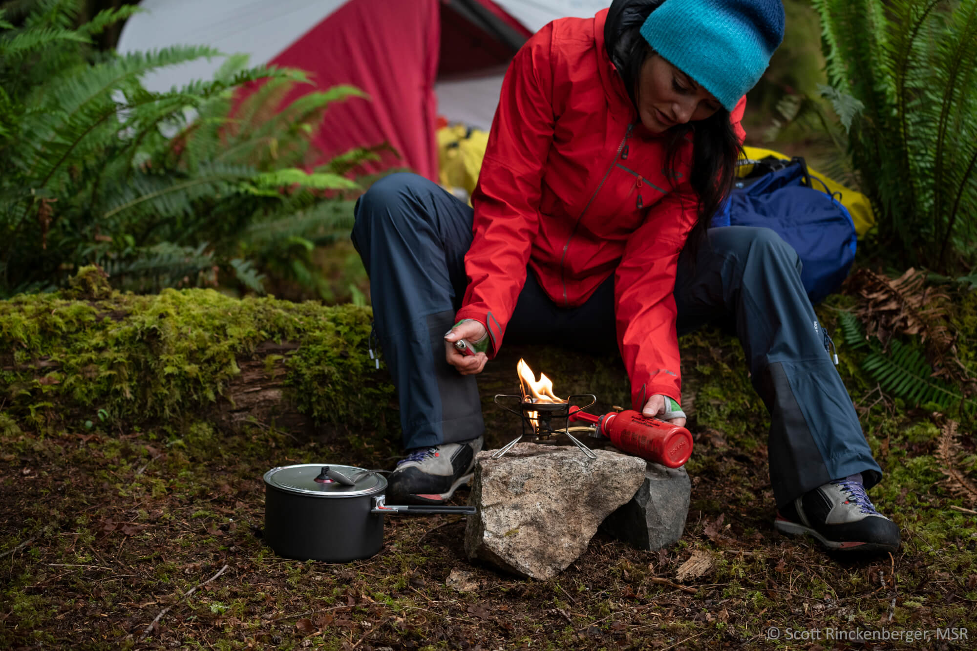 Eine Frau baut einen MSR-Kocher auf im Wald. Der Topf steht griffbereit neben ihr. Im hintergrund steht ein MSR-Zelt.