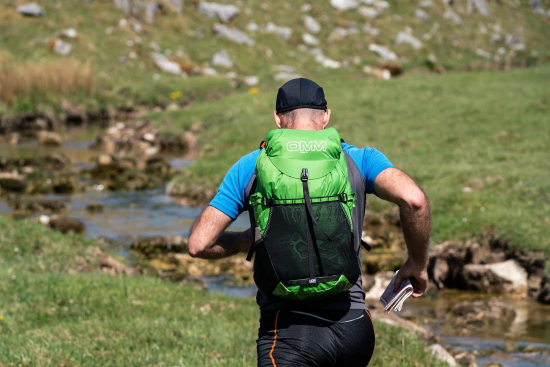 Ein Mann läuft an einem Fluss entlang. Er trägt ein blaues T-Shirt und einen grünen OMM-Rucksack