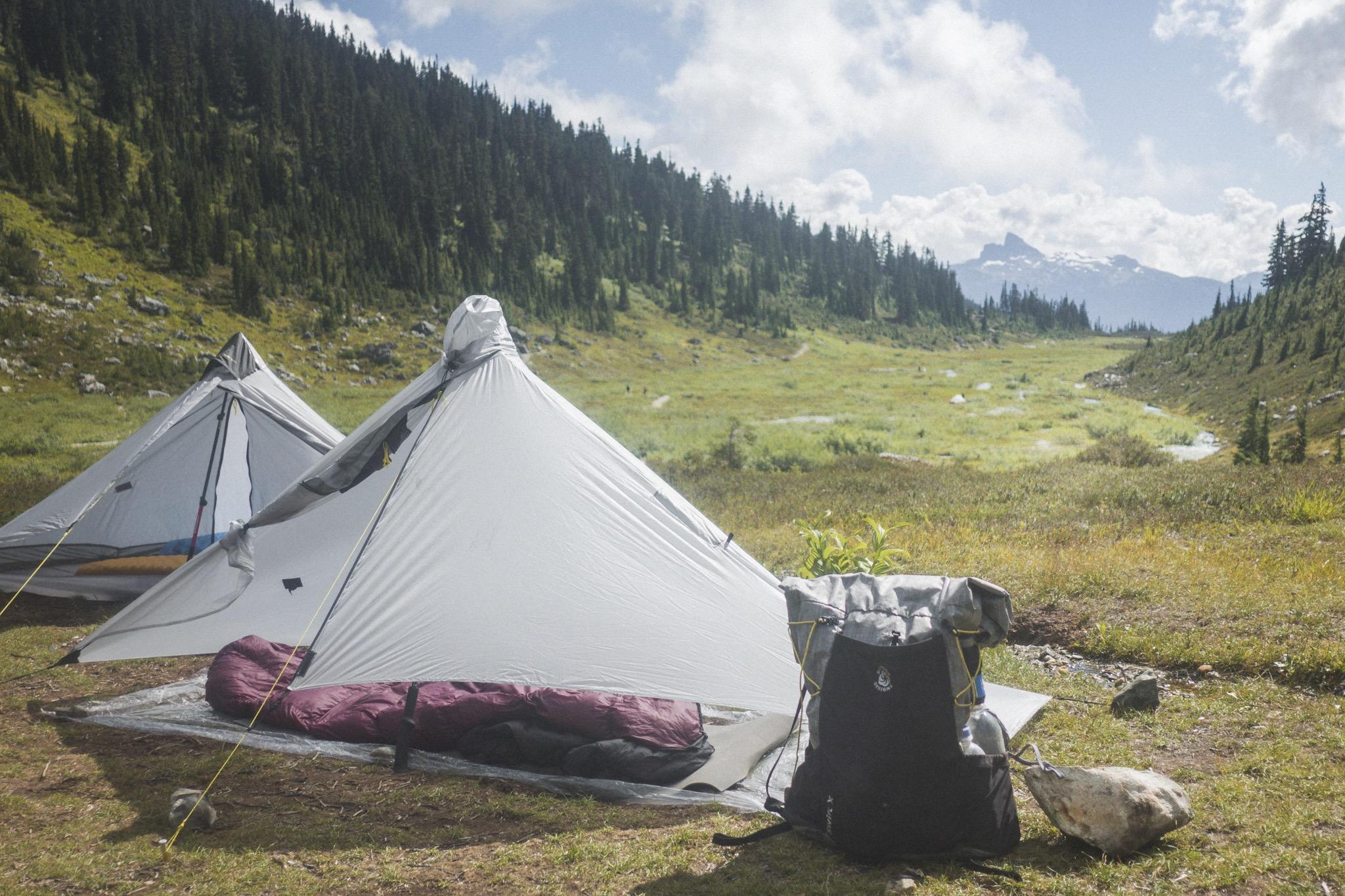 Six Moon Designs Zelt vor weiter Landschaft, links und rechts ziehen sich bewaldete Hänge hinauf