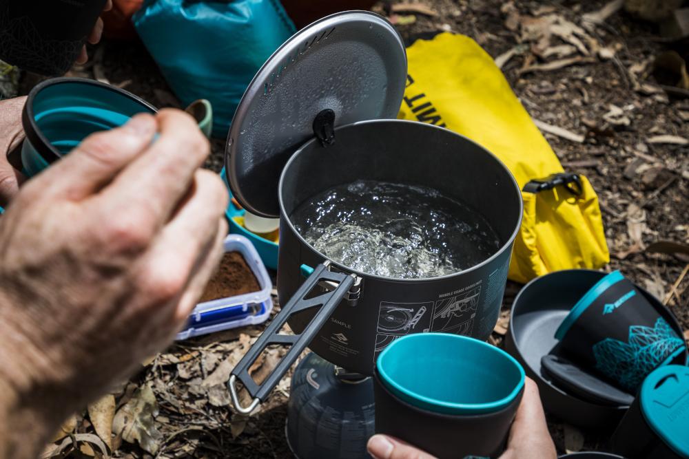 In einem Topf kocht Wasser. Hände halten blaue Sea-to-Summit Becher daneben. Kaffee steht in einer Dose daneben.