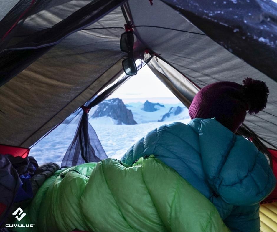 Eine Frau liegt eingehüllt in einen Cumulus-Schlafsack im Zelt. Es ist Winter