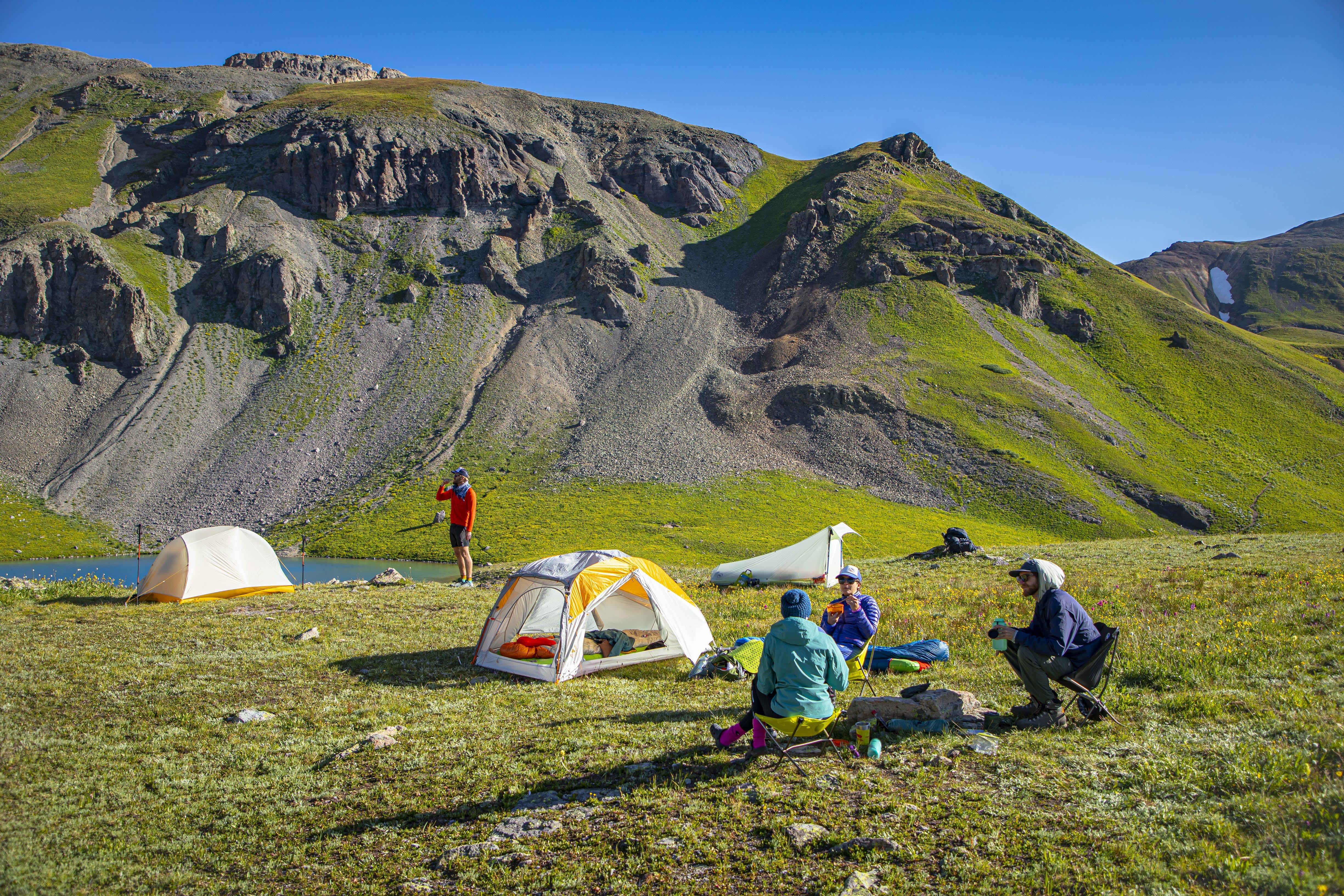 Big agnes Zelte stehen auf einer Wiese. Menschen bauen das Camp auf. Im Hintergrund sind Berge zu sehen. Die Sonne scheint.