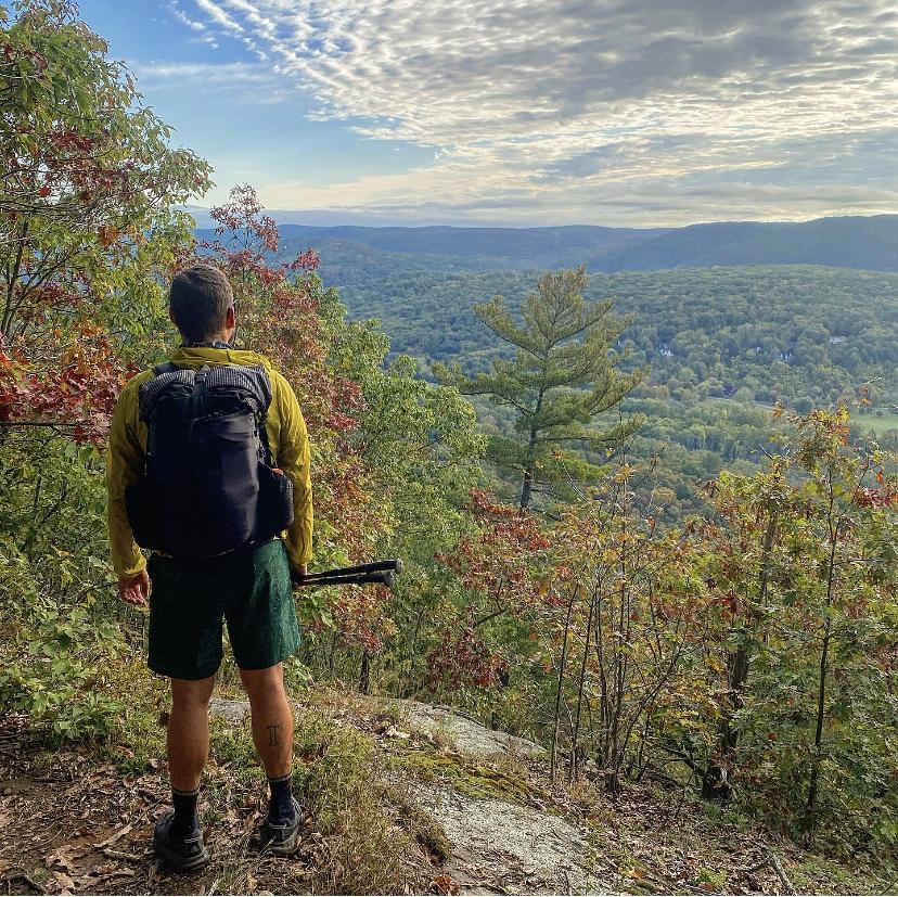 Ein Mann steht an einem Felsvorsprung und schaut über das Tal. Links steht ein Baum. Der Man trägt einen ULA Rucksack