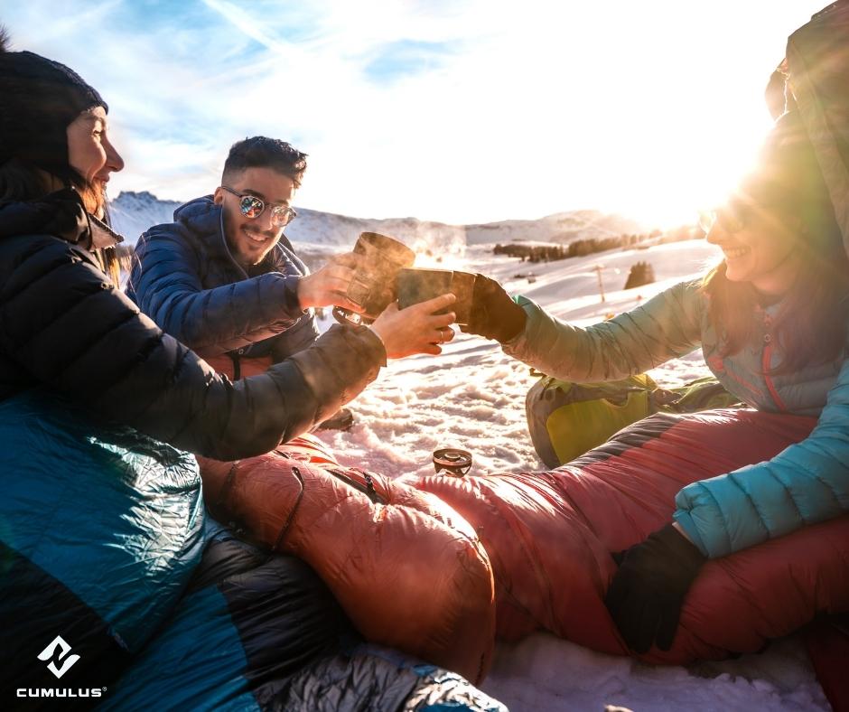 Eine Gruppe von Menschen sitzt im Winter draußen, eingehüllt in Cumulus Schlafsäcke und mit Tee in der Hand. Der Tee dampft.