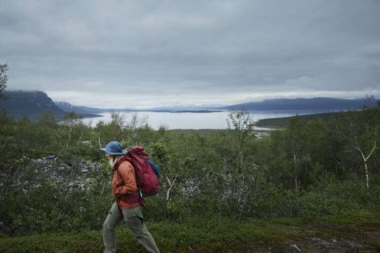 Eine Person wandert mit rotem Brimer Rucksack durch eine skandinavische Lanbdschaft. Im Hintergrund ist ein See, der Himmel ist wolkenverhangen.