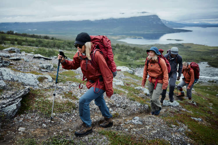 Gruppe von Menschen in skandinavischer Landschaft, alle tragen Outdoorkleidung in gedecktem rot oder orange. Sie tragen Rucksäcke