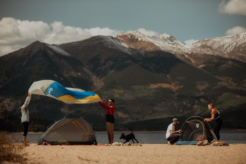 Menschen bauen an einem See Zelte von Sierra Designs auf. Eines ist halbfertig, bei dem zweiten wird gerade das Fly übergeworfen. Im Hintergrund sind Berge