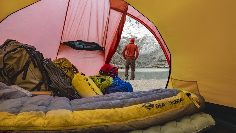 Blick aus einem gelben Zelt auf einen Wanderer der am See steht. Im Zeltinneren liegen ein Sea-to-Summit Schlafsack sowie Ausrüstung zum Klettern.